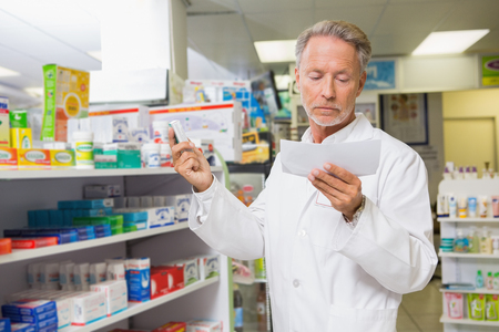 concentrated: Concentrated pharmacist reading prescription in the pharmacy