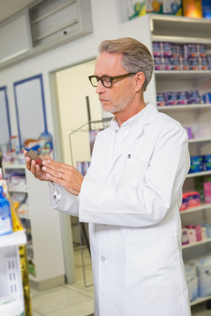 concentrated: Concentrated pharmacist looking at medicine in the pharmacy Stock Photo