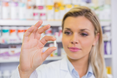 bata de laboratorio: Estudiante sonriente en bata de laboratorio sosteniendo la p�ldora en la farmacia Foto de archivo