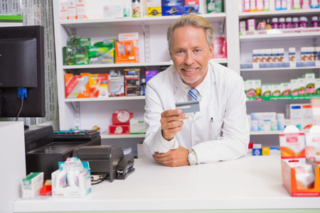 man holding card: Smiling senior pharmacist holding credit card in the pharmacy