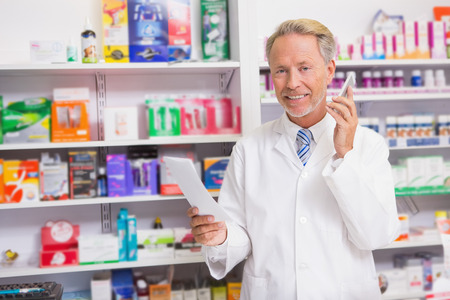 phoning: Smiling senior phoning while reading prescription in the pharmacy