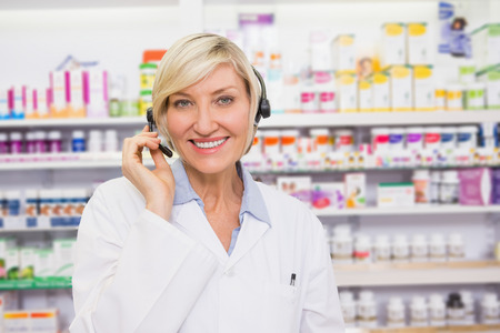 Pharmacist with headphone smiling at camera in the pharmacy photo
