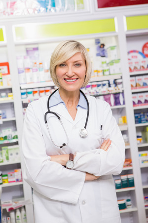 Smiling doctor with stethoscope and arms crossed in the pharmacy photo