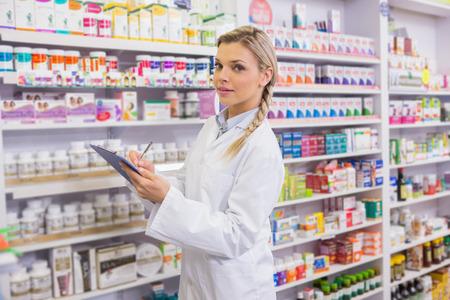 intern: Pharmacy intern writing on clipboard in the pharmacy