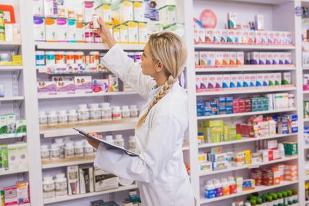 Junior apotheker het innemen van medicijnen van plank in de apotheek