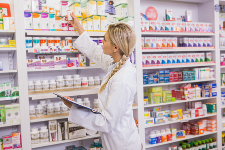 Junior pharmacist taking medicine from shelf in the pharmacy