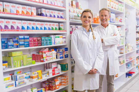 Apotheker met zijn stagiaire draagkracht en lachend naar de camera in de apotheek Stockfoto
