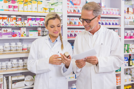 trainee: Pharmacist and trainee talking together about medication in the pharmacy