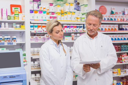 trainee: Pharmacist and trainee talking together about prescription in the pharmacy