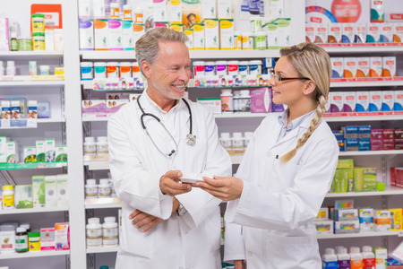 trainee: Pharmacist speaking with his trainee about medicine in the pharmacy