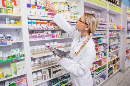farmacia: J�nior farmac�utico de tomar el medicamento de estante en la farmacia