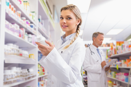 female portrait: Smiling student holding medicine in the pharmacy