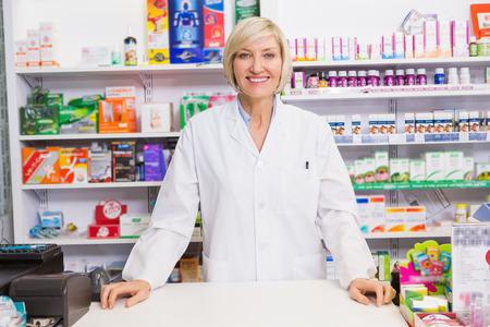 farmacia: Farmac�utico sonriente que presenta detr�s del mostrador de la farmacia