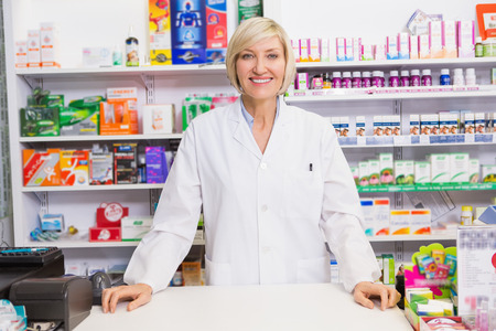 a jar stand: Smiling pharmacist posing behind the counter in the pharmacy