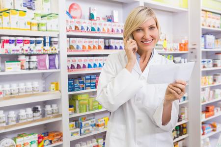 pharmacist: Smiling pharmacist on the phone reading prescription in the pharmacy Stock Photo