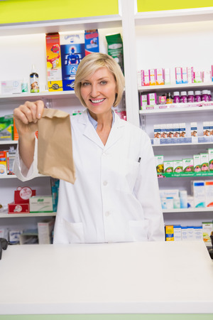 doctor giving glass: Smiling pharmacist showing envelope at the camera in the pharmacy