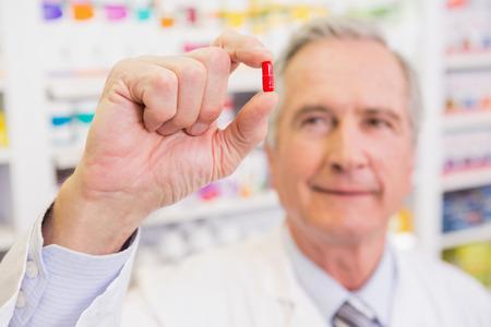 lab coat: Sonriendo farmacéutico en bata de laboratorio que muestra la píldora en la farmacia