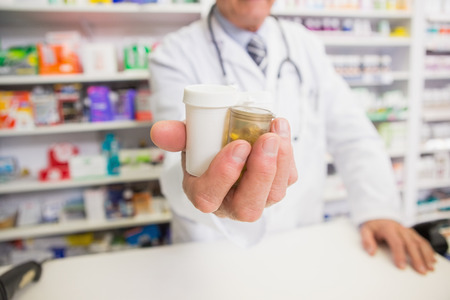 pharmaceutics: Pharmacist presenting medications on his hand in the pharmacy Stock Photo