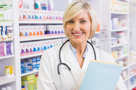Smiling doctor with stethoscope holding files in the pharmacy photo