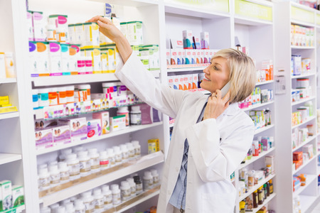 pharmacist: Smiling pharmacist phoning and taking medicine from shelf in the pharmacy