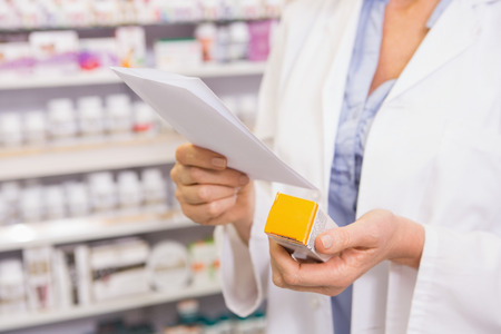 pharmacist: Pharmacist looking at prescription and medicine in the pharmacy