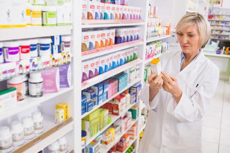 farmacia: Farmac�utico sonriente mirando a la medicina en la farmacia Foto de archivo
