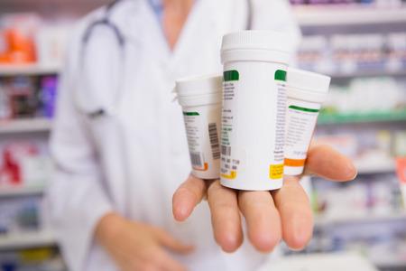 Apotheker presentatie van medicijnen op haar hand in de apotheek