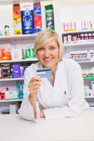 holding credit card: Smiling pharmacist holding credit card  in the pharmacy Stock Photo