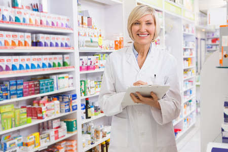 Smiling pharmacist writing on clipboard in the pharmacy