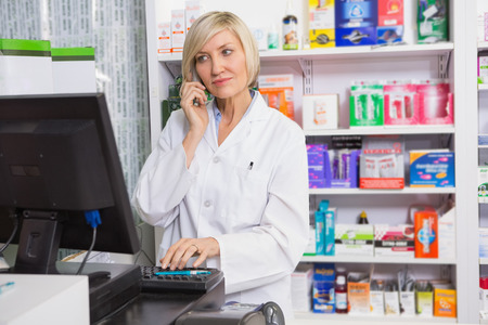 phoning: Blonde pharmacist using computer while phoning in the pharmacy Stock Photo