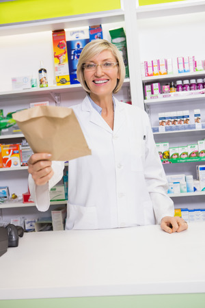 Smiling pharmacist showing envelope at the camera in the pharmacy photo