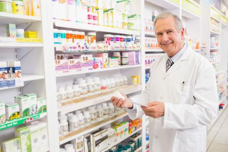 farmacia: Farmacéutico sonriente mayor celebración de la medicina y la prescripción en la farmacia Foto de archivo