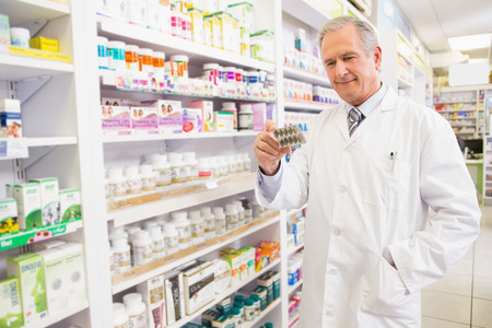 farmacia: Mayor sonriente farmac�utico blister sosteniendo en la farmacia