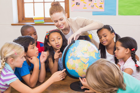 studying classroom: Cute pupils and teacher in classroom with globe at the elementary school Stock Photo