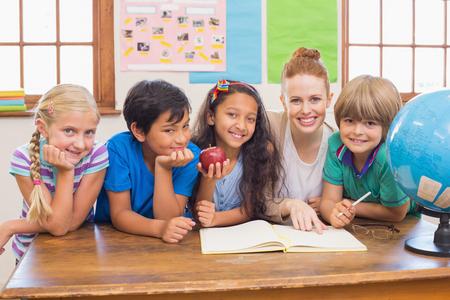 manzana: Alumnos lindos y profesor sonriendo a la c�mara en el aula en la escuela primaria Foto de archivo