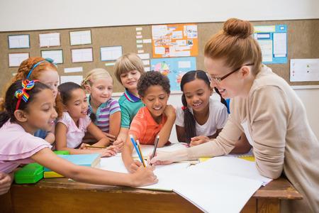 Leraar en leerlingen werken aan het bureau samen op de lagere school