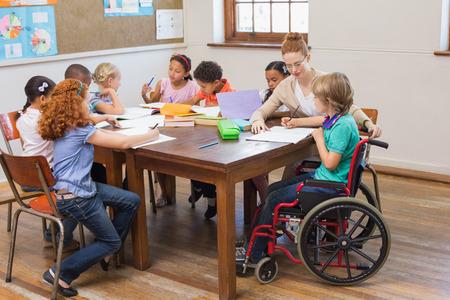 초등학교에서 교실에서 학생을 돕는 예쁜 선생님