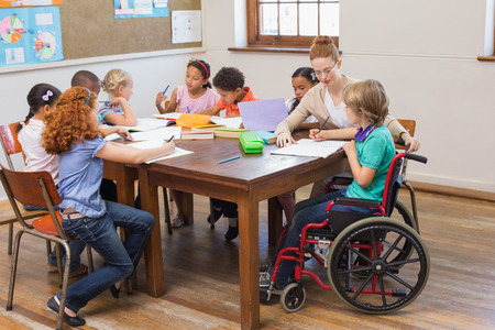 personas discapacitadas: Pretty profesor de ayudar a los alumnos en el aula en la escuela primaria Foto de archivo