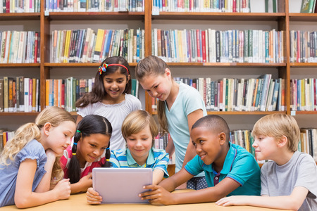 futuristic girl: Cute pupils using tablet computer in library at the elementary school Stock Photo