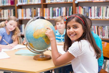 niños en la escuela: Alumnos lindos que miran el globo en la biblioteca en la escuela primaria Foto de archivo