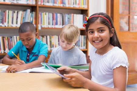 niño escuela: estudiante linda con tablet PC en la biblioteca en la escuela primaria