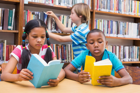 child reading book: Cute pupils reading in library at the elementary school