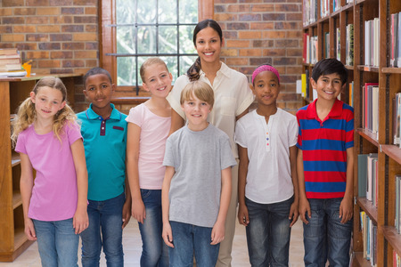 escuela primaria: Alumnos lindos sonriendo a la c�mara en el aula en la escuela primaria Foto de archivo