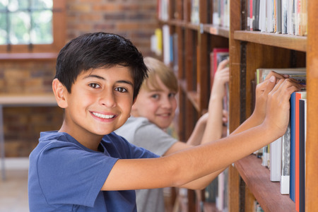 early childhood: Cute pupils looking for books in library at the elementary school Stock Photo