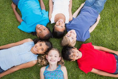 girotondo bambini: Amici felici che giocano nel parco in una giornata di sole