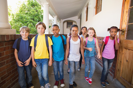 Cute pupils walking down the hall at the elementary school photo