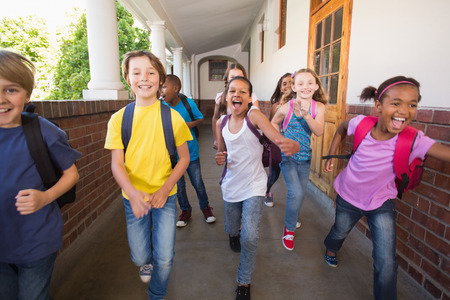 Cute pupils running down the hall at the elementary school photo