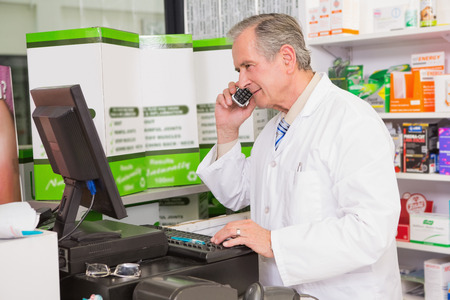 phoning: Senior pharmacist phoning while using computer in the pharmacy