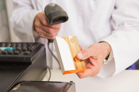 scanning: Pharmacist scanning medication with a scanner in the pharmacy