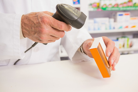 pharmacist: Pharmacist scanning medication with a scanner in the pharmacy